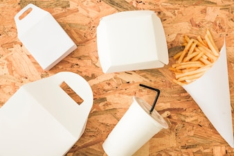 French fries; disposal cup and packages on wooden background