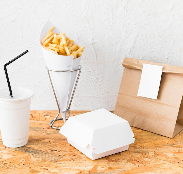 French fries; disposal cup; and food package on wooden desk