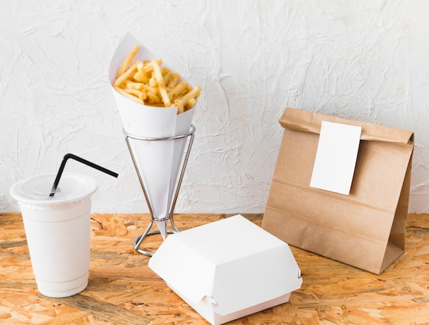 French fries; disposal cup; and food parcel on wooden surface