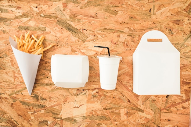 French fries; disposal cup and packages in a row on wooden table