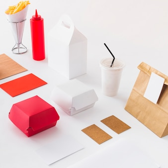 French fries; disposal cup; sauce bottle and food parcel on white surface