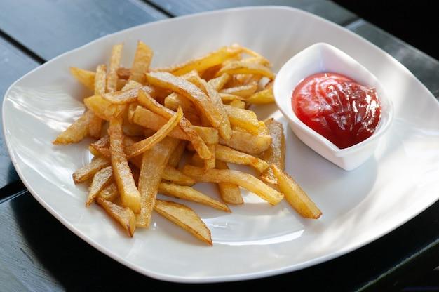 Картофель фри, вилки, стол. картофель фри на столе в открытом кафе. фаст-фуд, летнее кафе.