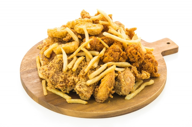 French fries and fried chicken on wooden plate