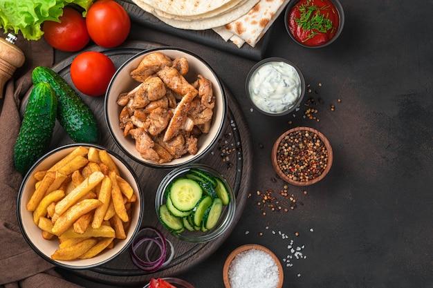 Картофель фри, жареное мясо, огурцы, помидоры и салат на коричневой стене с пространством для копирования. обед или ингредиенты для шаурмы, буррито, гироскопа.