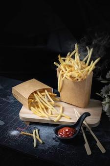 연기와 함께 검은 배경에 노란색 튀긴 감자 튀김