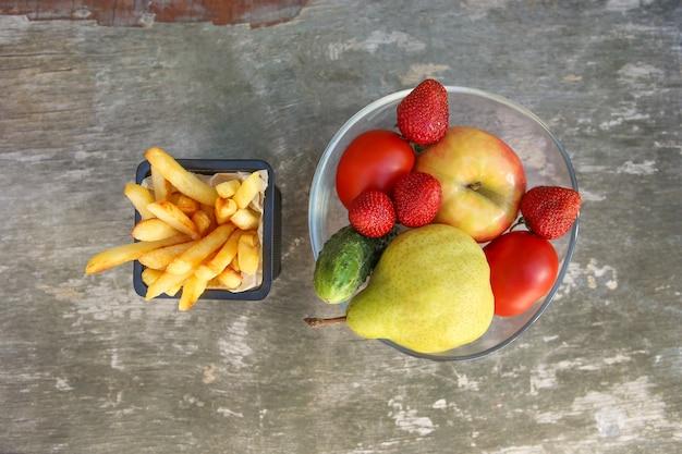 古い木製の背景にフライドポテト、果物、野菜。正しい栄養またはがらくたを食べることの概念。上面図。