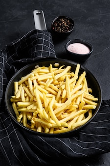 French fries in a frying pan. black background. top view