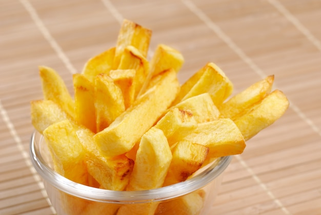 French fries in the glass bowl on wood table