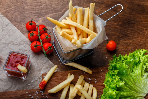 French fries in a grid with ketchup, salad and cherry tomatoes on wooden brown table