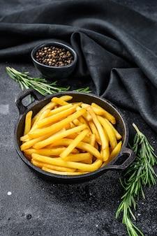 Картофель фри на сковороде, жареный картофель. черный фон. вид сверху.
