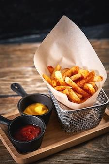 Картофель фри в корзине с кетчупом и соусом, изолированные на черном фоне