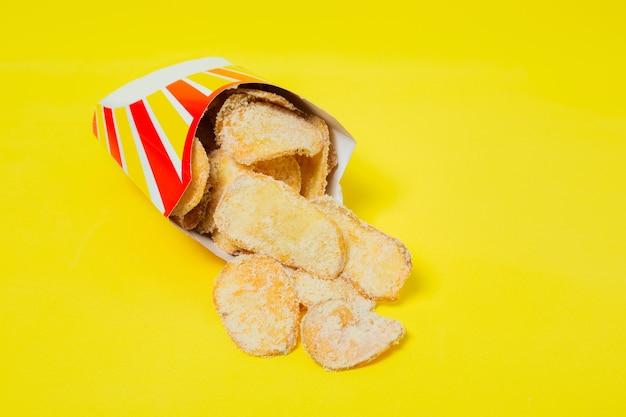 노란색 배경에 친환경 포장에 감자 튀김 건강에 해로운 패스트 푸드