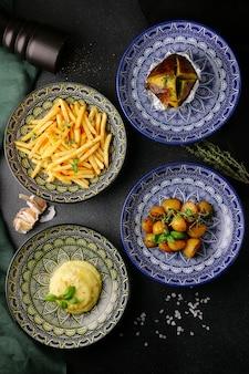 접시 평면도에 감자 튀김입니다. 다양한 감자 음식 평면도. 검은 콘크리트에 간식의 집합입니다.