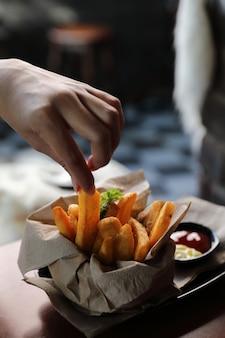 젊은 여자 손으로 나무 배경에 빈티지 스타일의 감자 튀김