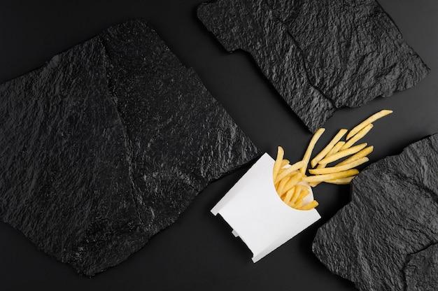 검은 돌 접시의 배경에 흰색 상자에 감자 튀김. 정상에서 보기