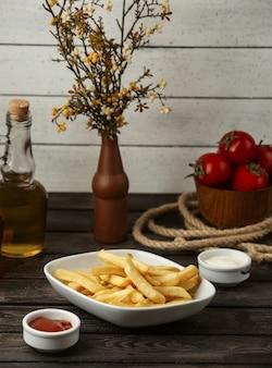 Ketchup e maionese delle patate fritte su una tavola di legno