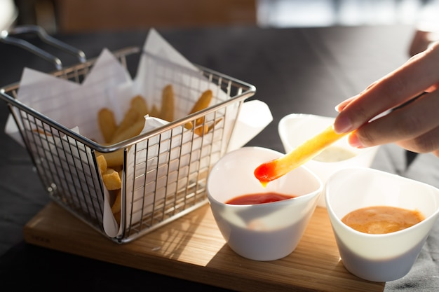 French fries in a metal basket with sauce on a wooden floor.