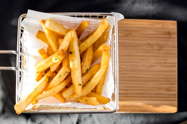 French fries in a metal basket on a wooden floor.