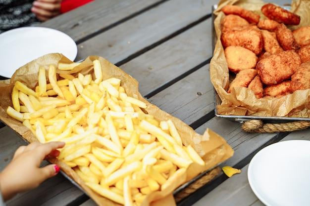 French fries and nuggets on the wooden table.