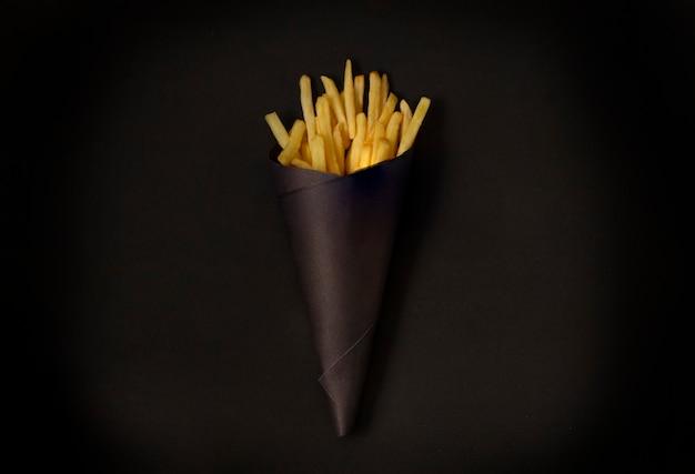 Картофель фри на черном столе, в черной упаковке, горизонтальный