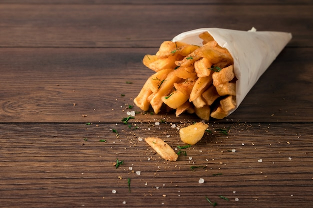 French fries, in a paper bag on wood