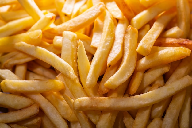French fries potato cooking deep fried in hot oil in basket of frying machine