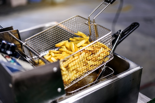 French fries potatoes cooking in basket of frying machine
