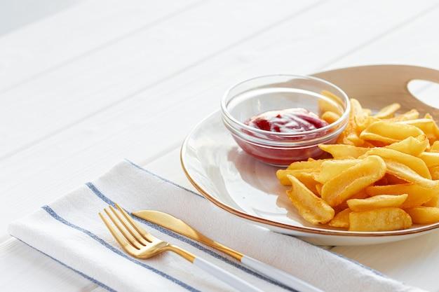Картофель фри в тарелке с соусом на деревянном столе