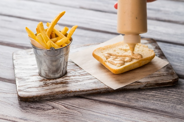 French fries in small bucket. bottle squeezes sauce on bread. first layer of delicious sandwich. preparation of food in bistro.