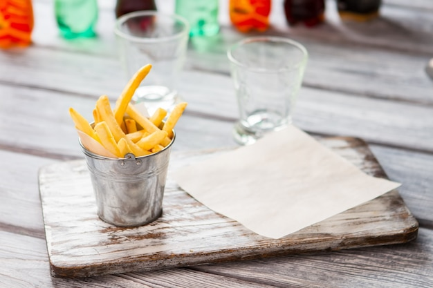 French fries in small bucket. gray wooden board. crispy snack made from potatoes. relax and have a bite.