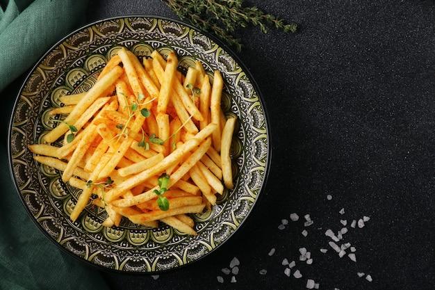 검은 콘크리트에 감자 튀김 최고 볼 수 있습니다. 소금과 녹색 접시에 맛있는 감자 튀김.