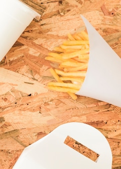 French fries in white cone on wooden textured backdrop