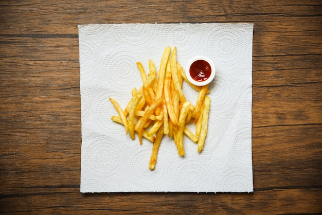 French fries on white paper with ketchup on wooden