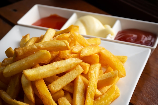 French fries on white plate served with chili, tomato sauce and mayonnaise.