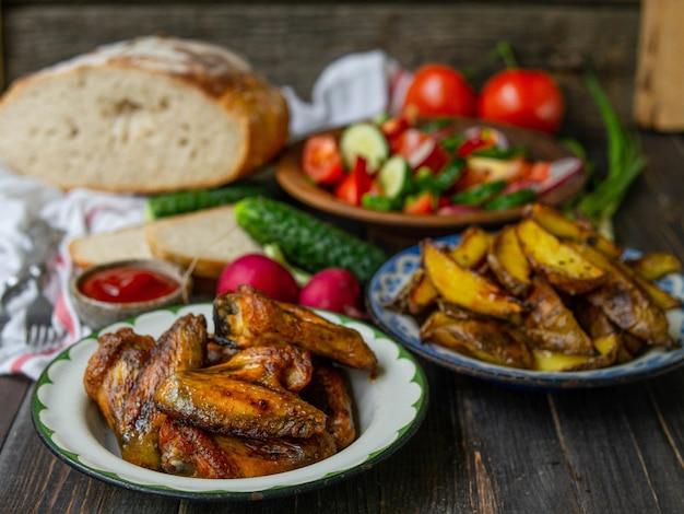 Картофель, крылышки, салат, овощи, хлеб на старом деревянном фоне. сельский ужин, летний пикник. вид сверху. плоская планировка.