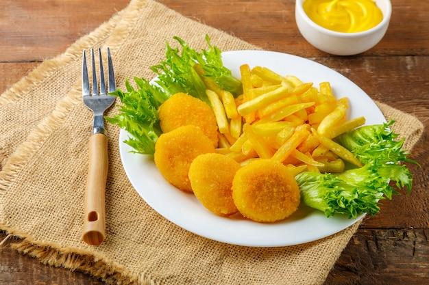 Картофель фри с куриными наггетсами в тарелке рядом с сырным соусом на деревянном столе на льняной салфетке. горизонтальное фото