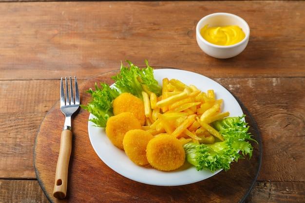 Картофель фри с куриными наггетсами в тарелке рядом с сырным соусом на деревянном столе на круглой подставке. горизонтальное фото