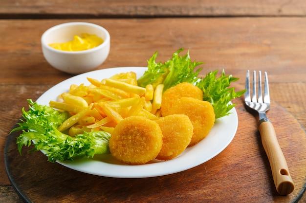 Картофель фри с куриными наггетсами в тарелке рядом с сырным соусом на деревянном столе на круглой подставке