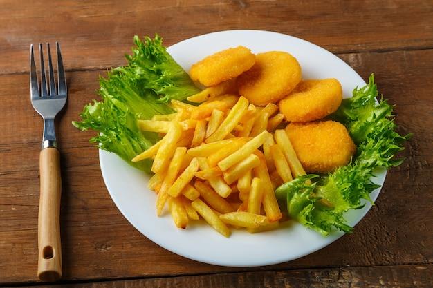 Картофель фри с куриными наггетсами в тарелке с зеленью рядом с деревянным столом рядом с вилкой. горизонтальное фото