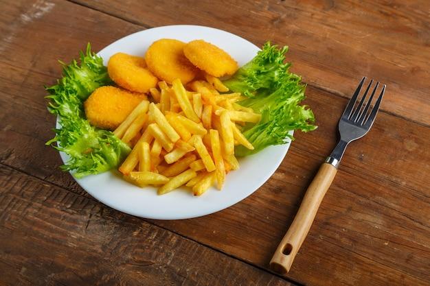 Картофель фри с куриными наггетсами в тарелке с салатом рядом с деревянным столом рядом с вилкой. горизонтальное фото