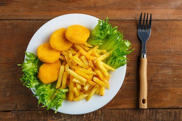 Картофель фри с куриными наггетсами в тарелке с салатом рядом с деревянным столом рядом с вилкой