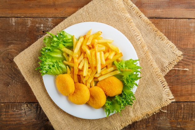 Картофель фри с куриными наггетсами в тарелке с салатом на деревянном столе на льняной салфетке