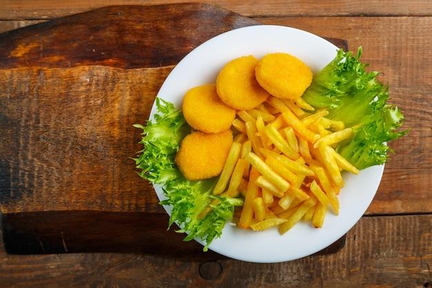 Картофель фри с куриными наггетсами в тарелке с салатом на деревянном столе на подставке