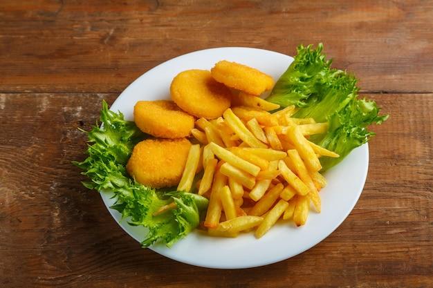 Картофель фри с куриными наггетсами в тарелке с салатом на деревянном столе