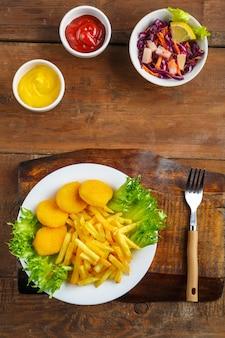 Картофель фри с куриными наггетсами рядом с сырным соусом и кетчупом в соуснике на деревянном столе.