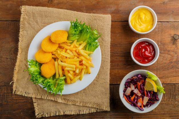 Картофель-фри с куриными наггетсами рядом с медленным соусом на салфетке на деревянном столе. горизонтальное фото