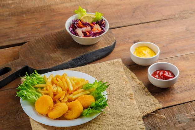 Картофель фри с куриными наггетсами возле соусов на салфетке на деревянном столе