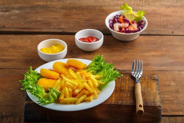 Картофель фри с куриными наггетсами рядом с сырным соусом и кетчупом в соуснике и салат на деревянном столе рядом с вилкой
