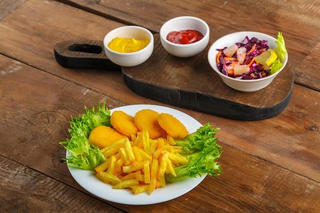 Картофель фри с куриными наггетсами рядом с сырным соусом и кетчупом в соуснике и салат на деревянных досках. горизонтальное фото