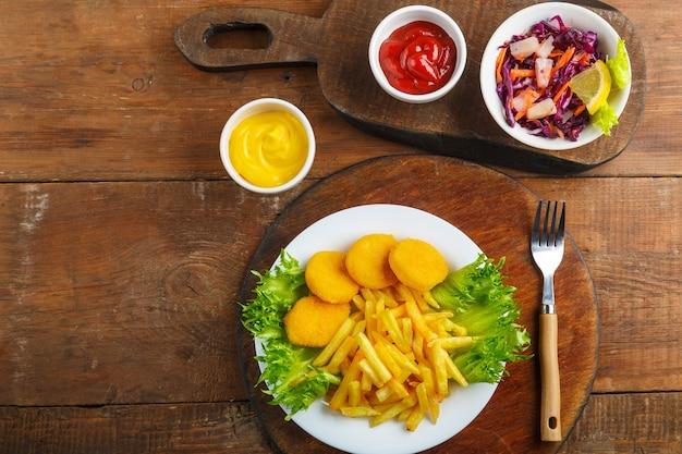 Картофель фри с куриными наггетсами рядом с сырным соусом и кетчупом в соуснике и салат на деревянных досках рядом с вилкой. горизонтальное фото